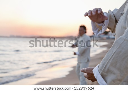 Two older people practicing Taijiquan on the beach at sunset, close up on hands - stock photo