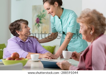 Two older women having a nice conversation with young nurse - stock photo