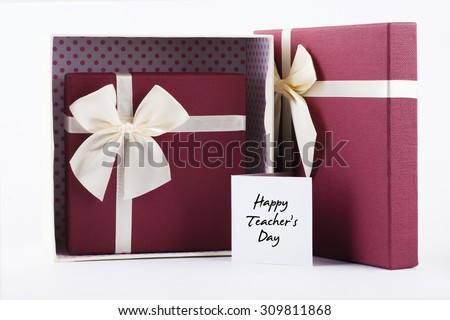 "Two open gift box with yellow ribbon with red heart shape gift box inside with ""Happy Teacher's Day"" words on white card - anniversary, valentine, birthday and couple concept"
