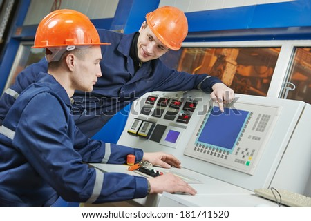 two operative industrial engineer workers discussing manufacture process near control panel system - stock photo