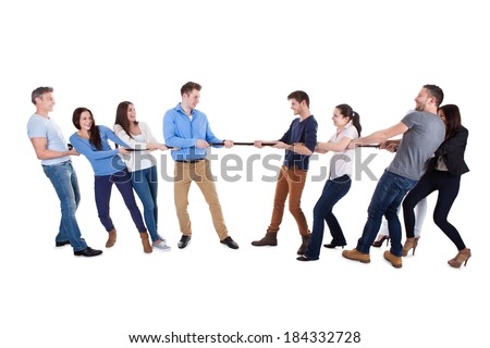 Two opposing teams having a tug of war pulling on opposite ends of a rope in a display of strength conceptual of competition  challenge and determination  on white - stock photo