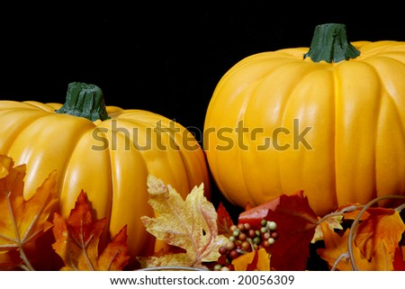 Two orange autumn pumpkins arranged on a black background with some leaves.