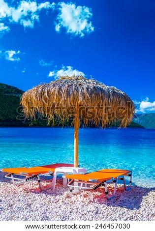 Two orange beach loungers and umbrella at tropical beach / Beach paradise - stock photo