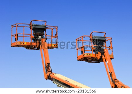 Two orange hydraulic platforms against the bright blue sky