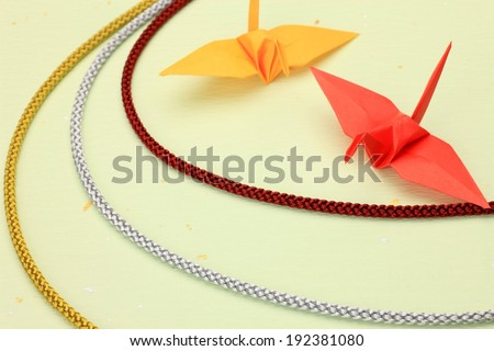 Two origami cranes alongside three different colored cords. - stock photo