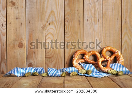 two original bavarian salted soft pretzels and hops with bavarian diamond pattern in front of weathered wooden board - stock photo