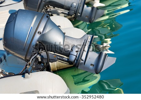 Two Outboard Boat Motors / Detail of two outboard used engines, on an inflatable boat on the water with reflections - stock photo