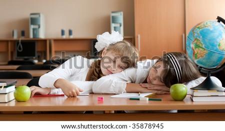 Two overworked preteen schoolgirls are sleeping on their desk - stock photo