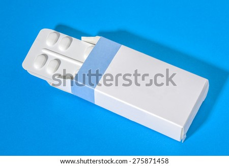 Two packages of pills inside a blue and white box - stock photo
