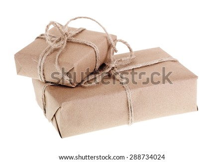 Two packages wrapped in brown paper and twine isolated on white - stock photo