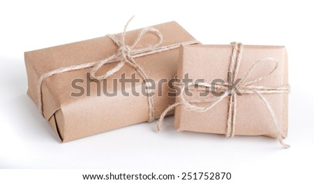 Two packages wrapped in brown paper tied with string on a white background - stock photo
