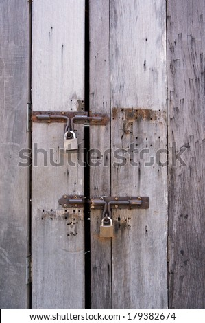 two padlock on a wooden door