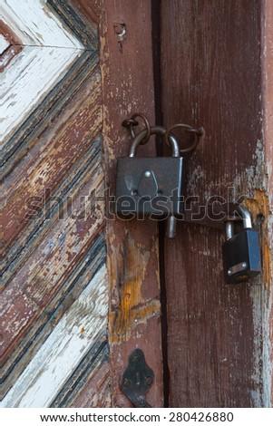 Two padlocks on old wooden door - stock photo