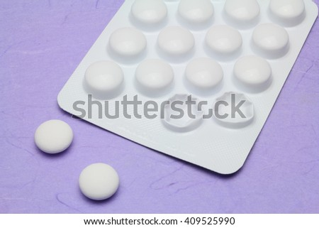 Two painkiller tablets from a blister pack - stock photo