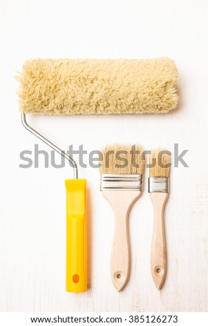 Two paint brushes and roller on white wooden background