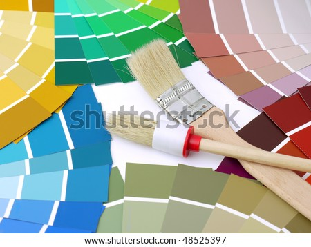 Two paint brushes on arrays of paint color swatches