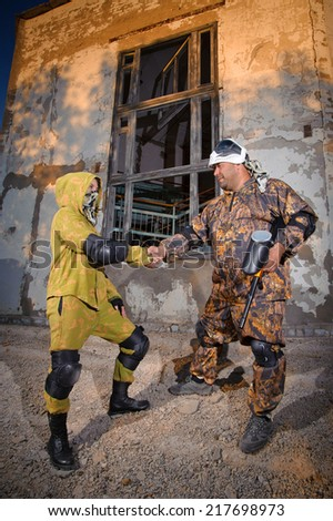 two paintball players in protective clothing aiming guns outdoors