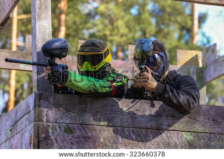 Two paintball shooters defending wooden tower - stock photo