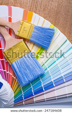 two paintbrushes on color palette and wooden board - stock photo