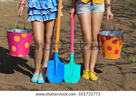 Two pair of female legs with buckets and shovels on garden