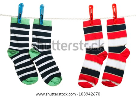 Two pair of striped socks hanging on the clothesline. Image isolated on white background - stock photo