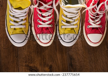 two pairs of cool youth red and yellow  gym shoes white laces   on brown wooden floor  standing in line with copy place  top view