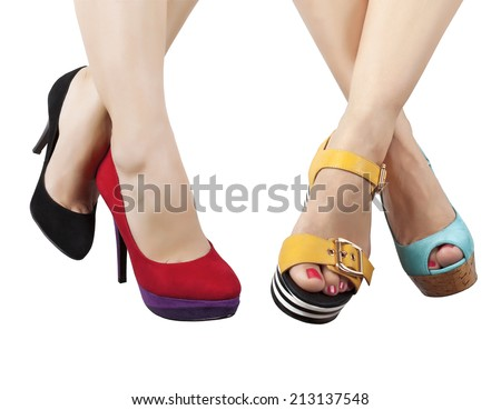 Two pairs of feet in different shoes and sandals - stock photo