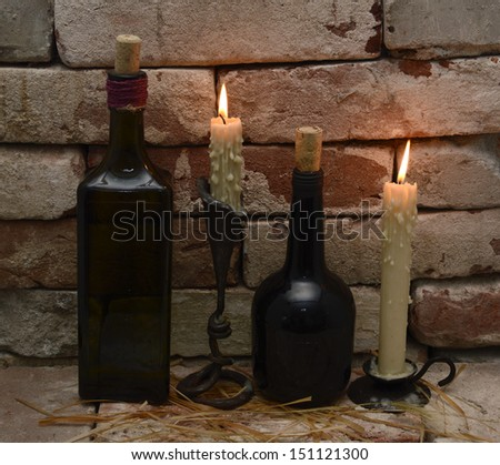 Two pairs of retro bottles and burning candles in gothic castle background - stock photo