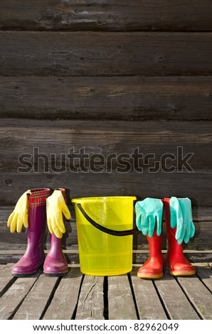 Two pairs of rubber boots, bucket and rubber gloves at sunny wooden verandah - stock photo
