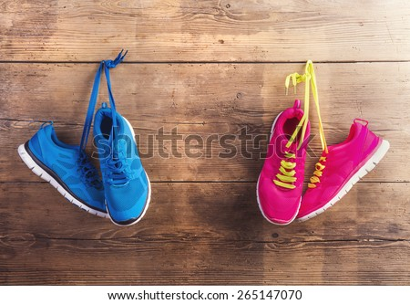 Two pairs of sneakers hang on a nail on a wooden fence background - stock photo