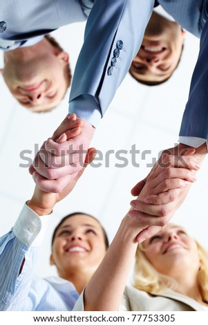 Two pairs of successful associates handshaking after striking deal with partners - stock photo