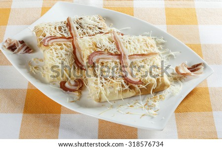 Two pancakes with savory filling served on a white plate with  bacon and grated smoked cheese. - stock photo