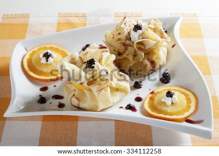 Two pancakes, wrapped as bags, with sweet filling served on a white plate with  blackberries, orange, lemon and whipped cream.  - stock photo