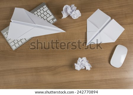 Two Paper Airplanes and balled up paper on a wooden office desk with modern keyboard and mouse - stock photo
