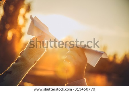Two paper airplanes in hands looking at each other at sunset - stock photo