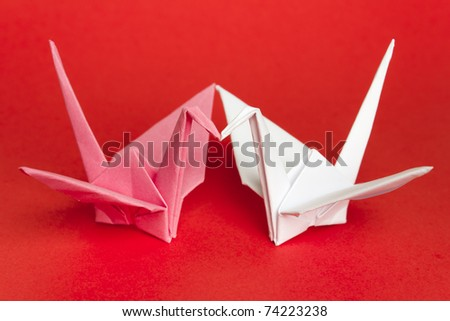 Two paper birds facing each other on a red background. Shallow depth of field. - stock photo