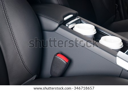 Two paper coffee cups standing in the car holder between seats