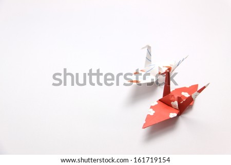 Two paper cranes on a white background. - stock photo