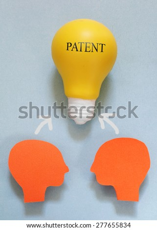 Two paper heads with a light bulb and Patent text                                - stock photo