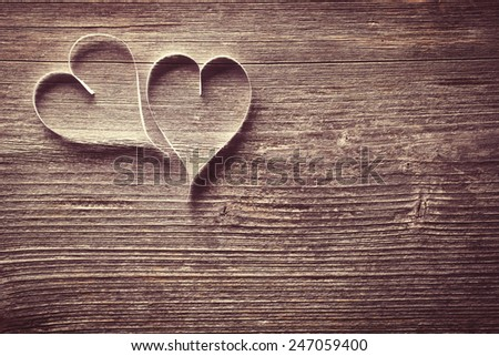 Two paper hearts on wooden background