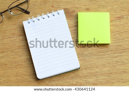 Two paper notes (white & yellow) on wood background, selective focus - stock photo