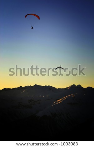 Two paragliders as silhouettes at sunset in the alps. - stock photo