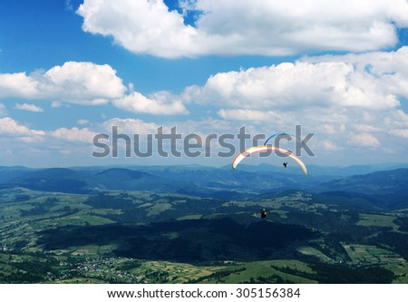 Two paragliders flying over summer mountains - stock photo