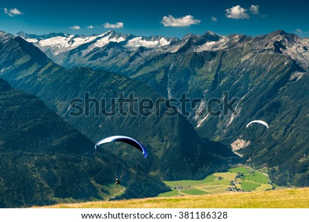 two paragliders flying over the green valley in the mountains with peaks and glacier view in the summer austrian alps near kaprun in salzburg - stock photo