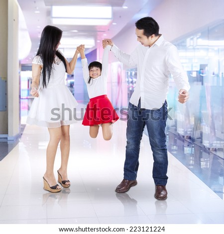 Two parents holding and lift their daughter in the mall - stock photo