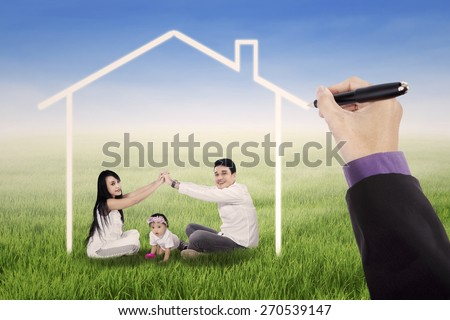Two parents playing on grass with their daughter under a dream house