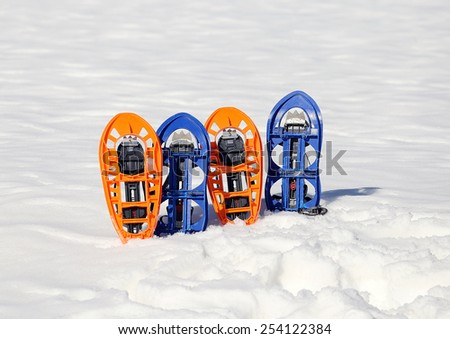 two pari of orange modern snowshoes in the mountain - stock photo
