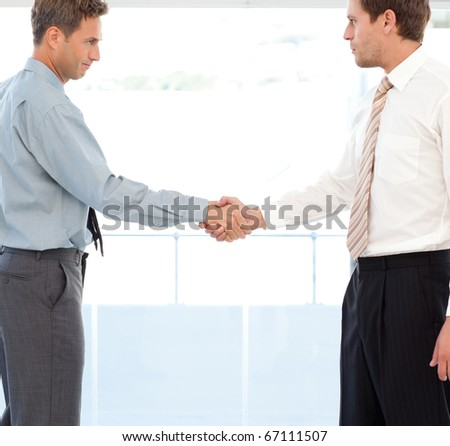 Two partners concluding a deal by shaking hands standing in the office - stock photo