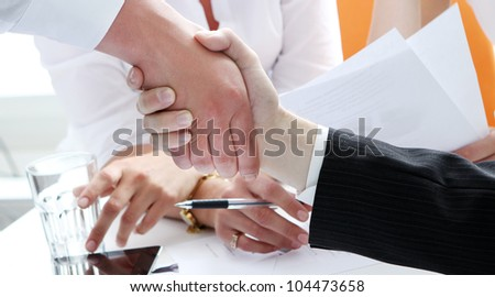 Two partners shaking hands at business meeting - stock photo