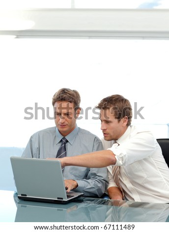 Two partners working together on a laptop sitting at a table in the office